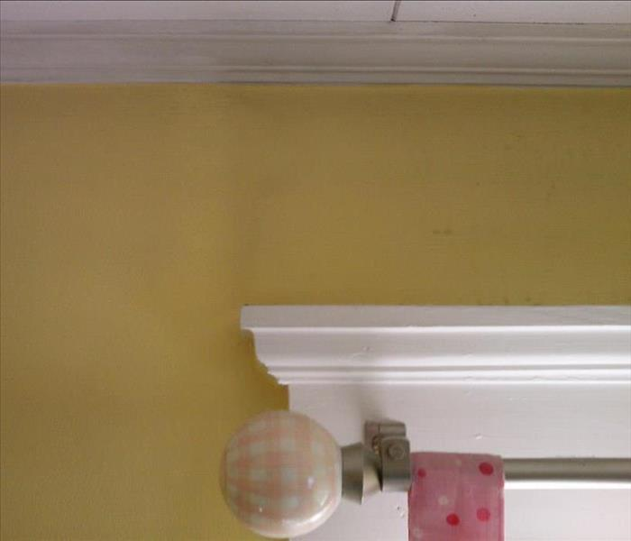 yellow wall with a curtain rod showing damage from soot