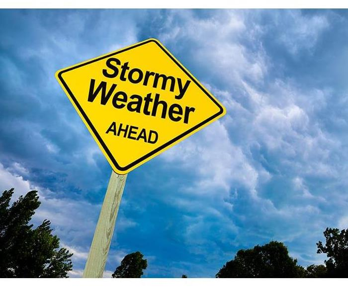 yellow street sign saying stormy weather ahead